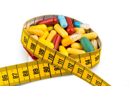 thinness: tablets and measuring tape, symbol for appetite suppressants, diet pills and slimming mania Stock Photo