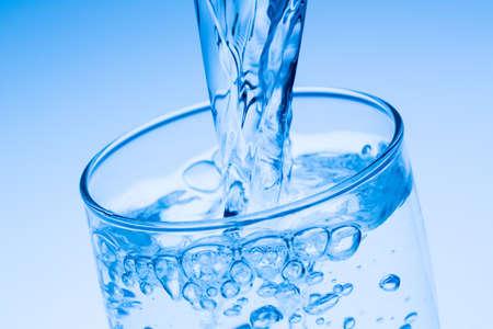 WATER GLASS: versare acqua in un bicchiere, foto simbolico per bere l'acqua, in eccesso e rifiuti Archivio Fotografico