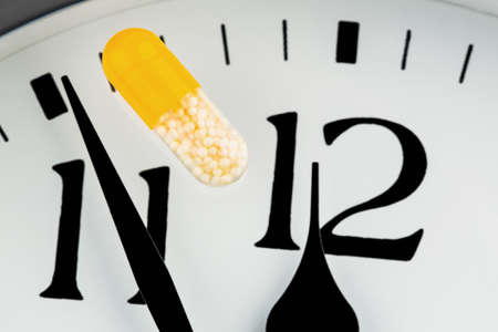 capsule on a clock, symbolic for healthcare, health reform, congestion photo