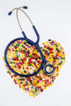 angina: estetoscopio y tabletas en una disposición en forma de corazón, símbolo de la enfermedad cardíaca, el diagnóstico y la medicación