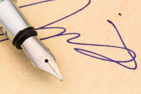 legacy: a fountain pen and a signature on yellow paper  symbolic for contract testament and graphology