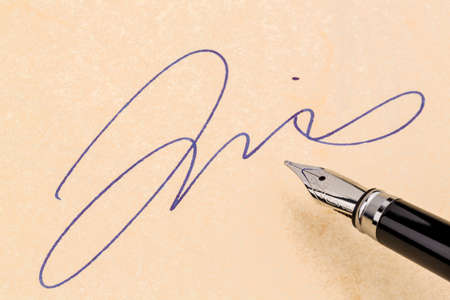 notieren: a fountain pen and a signature on yellow symbolic photo for contract testament and graphology Stock Photo