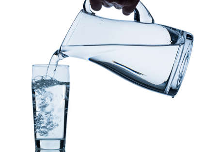 purely: pure water is emptied into a glass of water from a pitcher  fresh drinking water