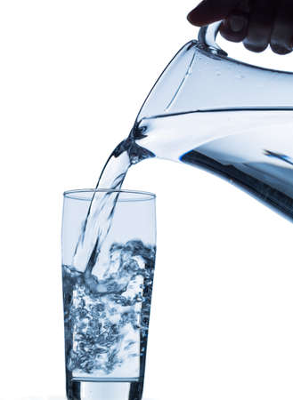 emptied: pure water is emptied into a glass of water from a pitcher  fresh drinking water