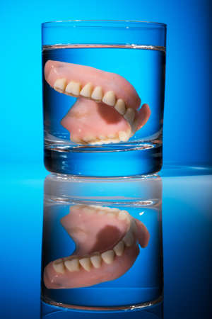 a denture is cleaned in a glass of water  proper hygiene  photo