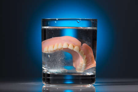 nursing class: a denture is cleaned in a glass of water  proper hygiene  Stock Photo