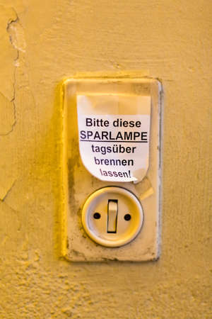 old light switch with label leave, saving lamp burning day photo