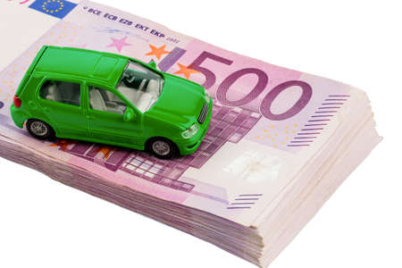 hidden taxes: green model car on banknotes, symbolic photo for car buying, financing and costs