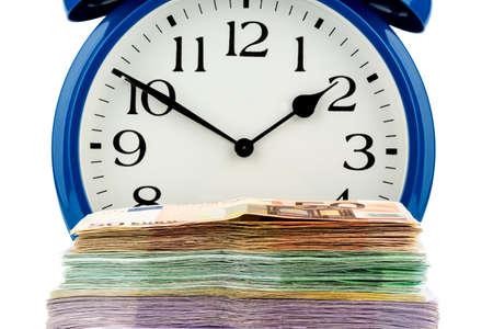 remuneraci�n: un despertador y billetes de banco, foto simb�lica de los costes salariales, los costos de mano de obra, tiempo de trabajo