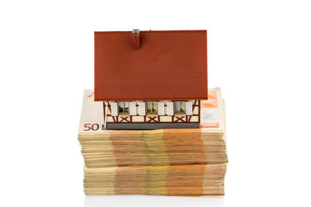 single familiy: half-timbered house on euro banknotes, symbolic photo for home purchase, financing, building society