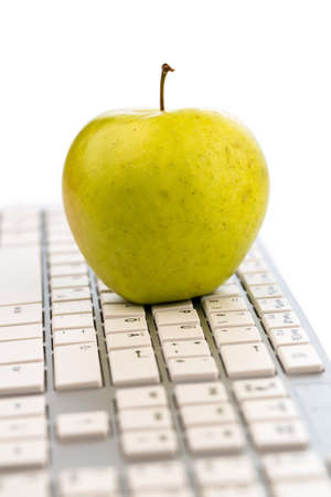 fast meal: an apple is on a computer keyboard  symbolic photo for healthy and vitamin-rich snack  Stock Photo