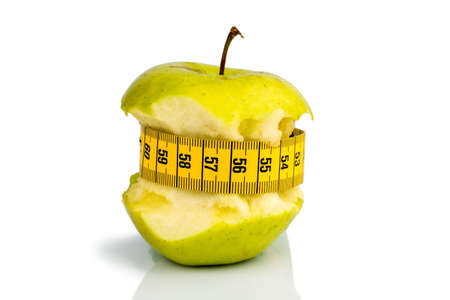 free weight: apple with a measuring tape  symbolic photo for diet and healthy, vitamin-rich diet  Stock Photo