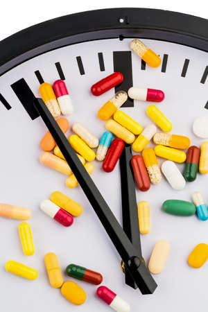 health reform: colorful capsules on a clock, symbolic photo for healthcare, health reform, congestion