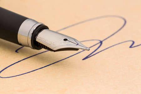 testament schreiben: einen Füllfederhalter und eine Signatur auf gelbem Papier symbolische Foto für Vertrag und Graphologie Testament