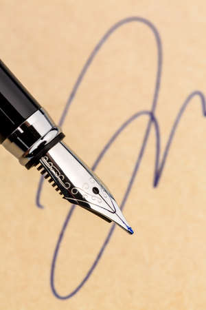 notieren: a fountain pen and a signature on yellow paper  symbolic photo for contract, and graphology testament Stock Photo