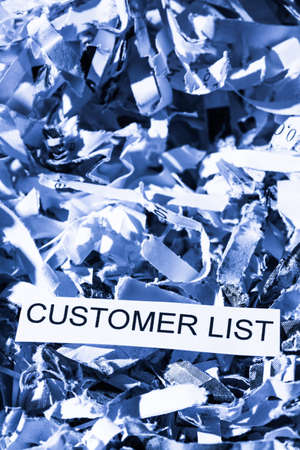paper shredder: scraps of paper with the word customer list, photo icon for data destruction, data protection and customer data
