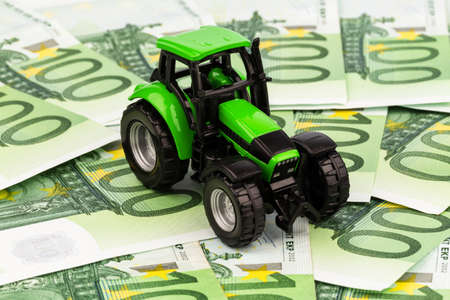profitability: a tractor standing on euro banknotes  symbol photo for costs, revenues and subsidies of farmers in agriculture