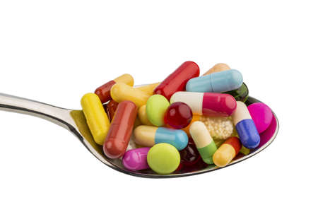 pill: many colorful pills on a spoon  symbolic photo for tablets addiction and abuse of drugs