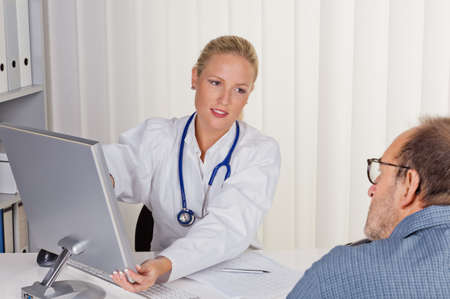 familiy: a young doctor with stethoscope in her doctor s office  in conversation with a patient Stock Photo