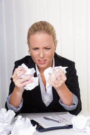 discouraged: a woman in the office with paper balls  anger, stress and frustration in the workplace