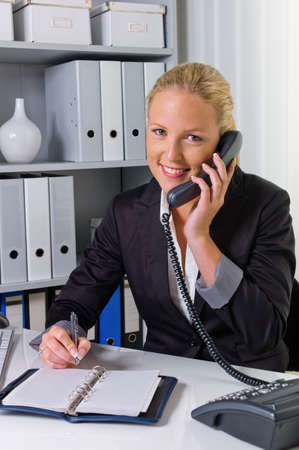 notieren: a friendly woman phone at her desk in the office and dates listed in the calendar