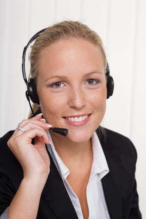 una mujer amable joven con auriculares de tel�fono de servicio al cliente con un cliente ventas amistosas asocian Foto de archivo - 19634642