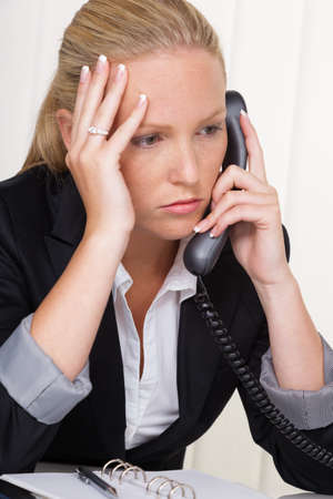 listless: a frustrated woman phoned the office  stress and strain in the workplace  Stock Photo