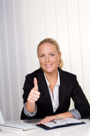 a young successful woman sitting at her desk in the office  photo
