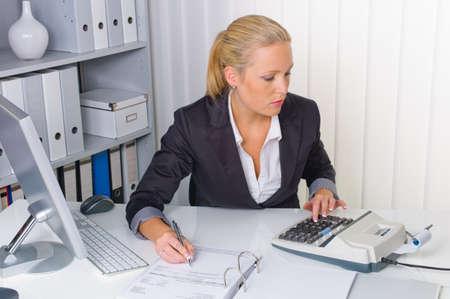 bookkeeping: un contador en el trabajo en la oficina con la calculadora