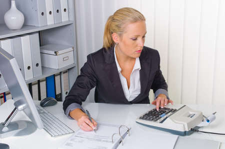 dichiarazione: un ragioniere al lavoro in ufficio con il calcolatore Archivio Fotografico