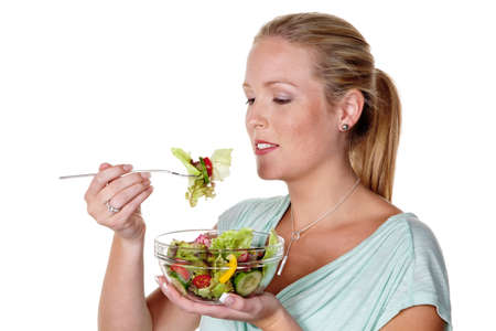eat right: a young woman eating a fresh salad at lunch  healthy diet with vitamins