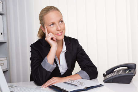 permission: a young, successful business woman sitting at her desk in the office