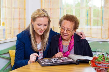 consider: a grandchild visiting his grandmother  view the photo album  Stock Photo