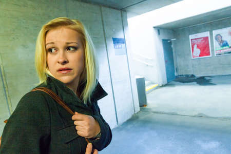 psique: una mujer joven en un paso subterr�neo para peatones tiene miedo del acoso y los delitos