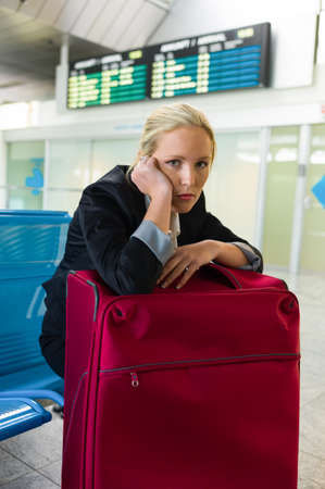 businesswoman waiting for their departure at the airport  symbolic photo for waiting times, flight cancellations and strikes  photo