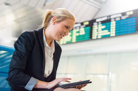 abroad: a businesswoman using her tablet computer at an airport  mobility and communication in business  roaming charges when abroad