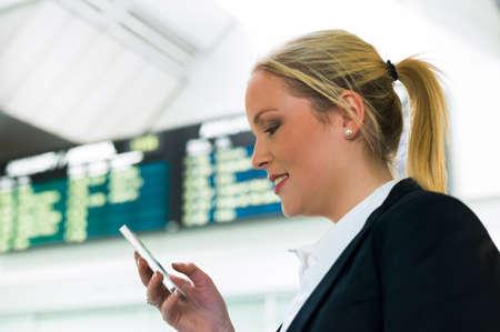 gente aeropuerto: Mujer de negocios escribe en sms aeropuerto tarifas de itinerancia en el extranjero accesibilidad con la tecnolog�a moderna