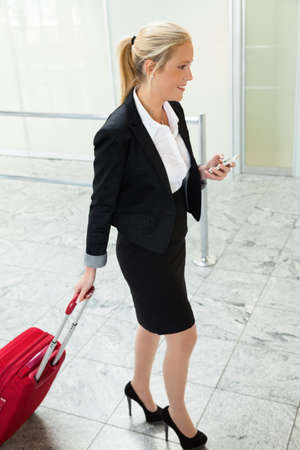 foreign country: a business woman with suitcase and smartphone at an airport  mobility and communication in business