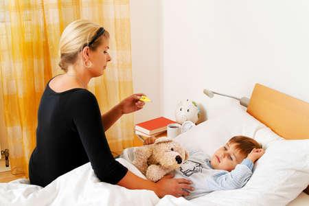 enfant malade: une mère et son enfant malade à la grippe lit dentition