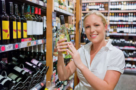 local supply: a woman buying wine in a supermarket  wine shelf with wines from around the world  Stock Photo