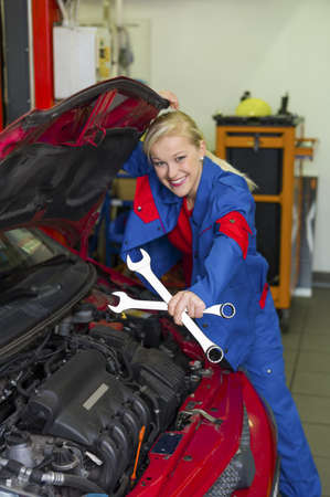 a young woman as a mechanic in a garage  rare professions for women  car is being repaired in the workshop Stock Photo - 19634551