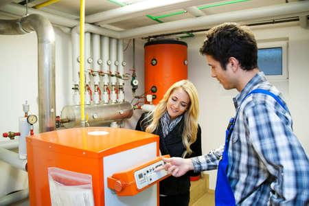 ordenanza: calefactor joven en sala de calderas para calefacci�n Foto de archivo