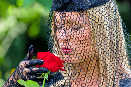 inherit: a young, grieving widow with veil and rose  death and inheritance  Stock Photo