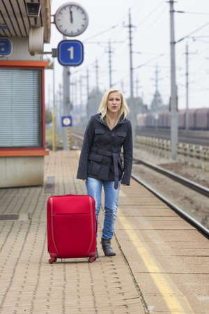 where to go: a young woman with suitcase waiting on the platform of a railway station on their train  train delays Stock Photo