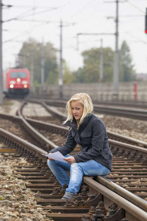 a young woman sitting on a track  holds farewell letter in his hand photo