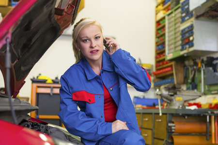 a young woman as a mechanic in a garage  rare professions for women  car is being repaired in the workshop photo
