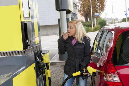 caras emociones: una mujer joven en un tanque de gas gasolina estaci?n del coste del coche debido a los precios del gas son cada vez m?s caro
