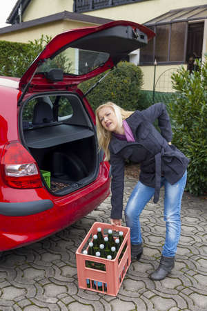 herniated: a young woman lifts a crate of bottles from their car  real life prevents back pain and herniated disc