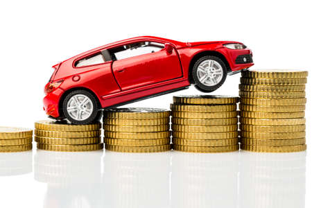 upkeep: a car standing on euro bills  cost of buying a car, gasoline, car insurance and other costs Stock Photo
