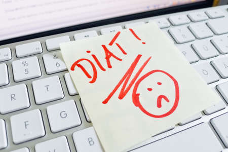 thinness: a sticky note on the keyboard of a computer is to remember  diet Stock Photo